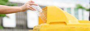 envase de agua de plástico en contenedor amarillo