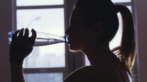 mujer joven bebe agua mineral en una botella a contraluz