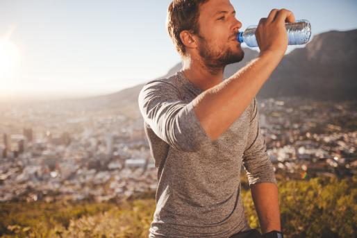 hombre joven bebe agua mineral tras senderismo