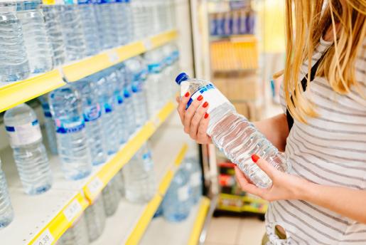 mujer comprando una botella de agua mineral