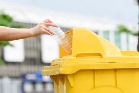 hombre recicla envase de plástico de agua mineral en contenedor amarillo