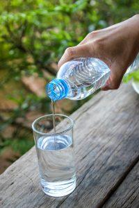 hombre virtiendo agua mineral en un vaso