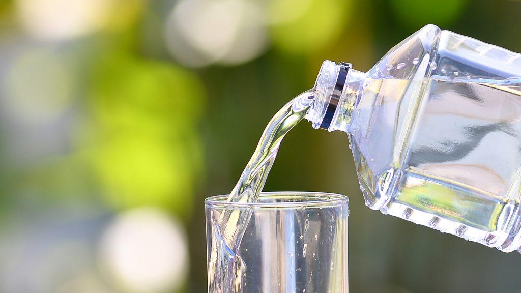 Botella de agua mineral sirviéndose en un vaso
