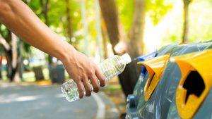 joven depositando un envase de agua en el contenedor amarillo