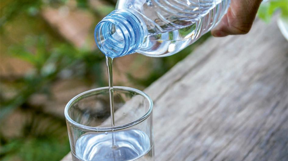 agua en una botella con ecodiseño llenando un vaso